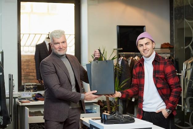 Een volwassen man met grijs haar en een sportieve lichaamsbouw neemt zwarte papieren zakken met aankopen van een verkoper in een kledingwinkel. een lachende winkelbediende en een mannelijke klant poseren met papieren zakken.