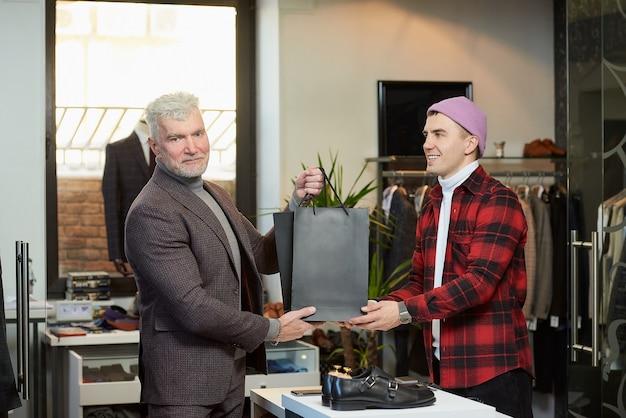 Een volwassen man met grijs haar en een sportieve lichaamsbouw neemt zwarte papieren zakken met aankopen van een verkoper in een kledingwinkel. een lachende winkelbediende geeft papieren zakken aan een mannelijke klant.