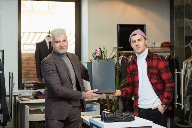 Een volwassen man met grijs haar en een sportieve lichaamsbouw neemt zwarte papieren zakken met aankopen van een verkoper in een kledingwinkel. een tevreden winkelbediende en een mannelijke klant poseren met papieren zakken