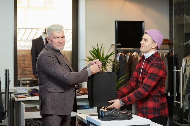 Een volwassen man met grijs haar en een sportieve lichaamsbouw neemt zwarte papieren zakken met aankopen van een verkoper in een kledingwinkel. een winkelbediende geeft papieren zakken aan een mannelijke klant.