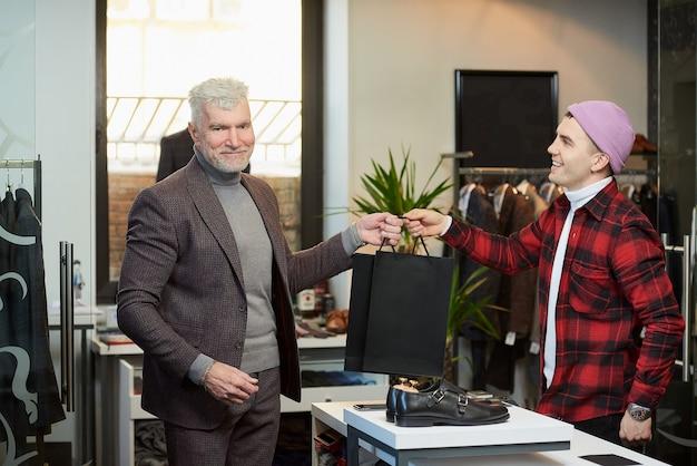 Een volwassen man met grijs haar en een sportieve lichaamsbouw neemt zwarte papieren zakken met aankopen van een verkoper in een kledingwinkel. een winkelbediende met een glimlach geeft papieren zakken aan een mannelijke klant.