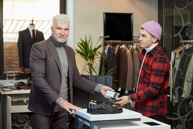 Een volwassen man met grijs haar en een sportieve lichaamsbouw past een mobiele telefoon toe op een verkooppunt in een kledingwinkel. een tevreden klant met een baard betaalt aan een winkelbediende in een boetiek