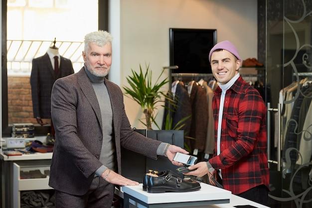 Een volwassen man met grijs haar en een sportieve lichaamsbouw past een mobiele telefoon toe op een verkooppunt in een winkel. een tevreden klant met een baard betaalt aan een lachende winkelbediende in een boetiek.