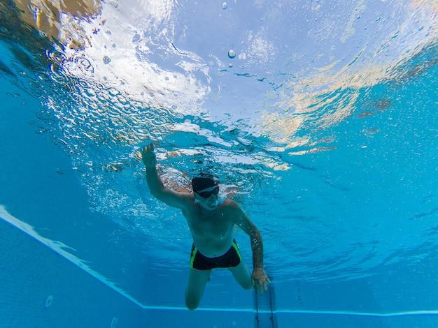Een volwassen man of senior training en oefening zwemmen in een zwembad alleen - onder water zicht op gepensioneerde zwemmen - actieve senior en gezonde levensstijl