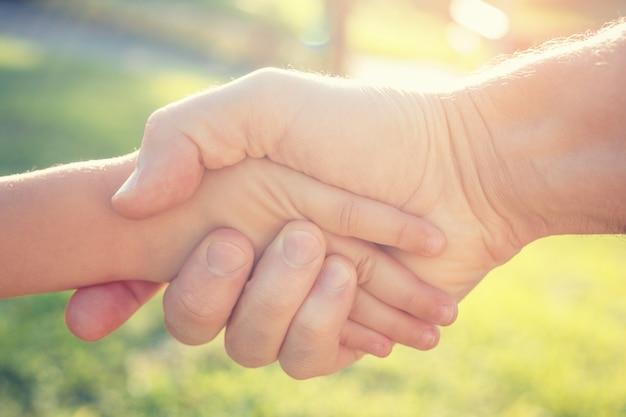 Een volwassen man schudt de hand met een kind. het concept van redding en hulp