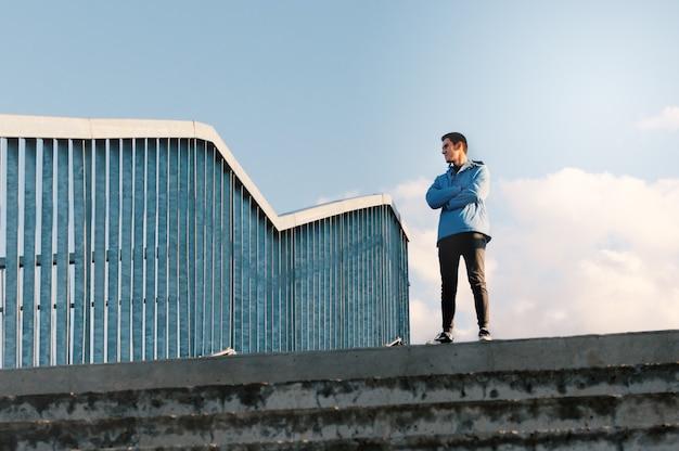 Een volwassen man staat op de brug, kruist zijn armen over zijn borst en kijkt in de verte.