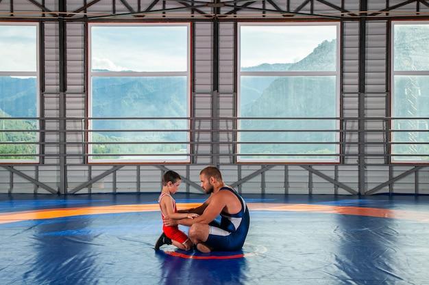 Een volwassen mannelijke worstelaarstrainer leert de basisprincipes van het worstelen