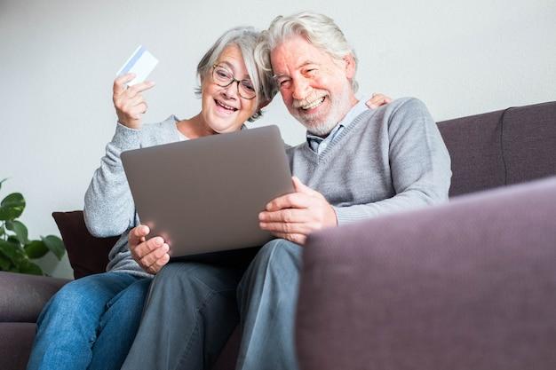 Een volwassen paar mensen op de bank die haar laptop en hun creditcard gebruiken om iets te kopen - online winkelen concept en shopaholic - senior thuis die geschenken en cadeautjes doet met de verkoop