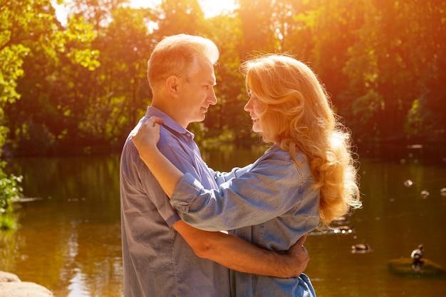 Een volwassen paar staan aan de oever van het meer in een omhelzing in de stralen van de ondergaande zon