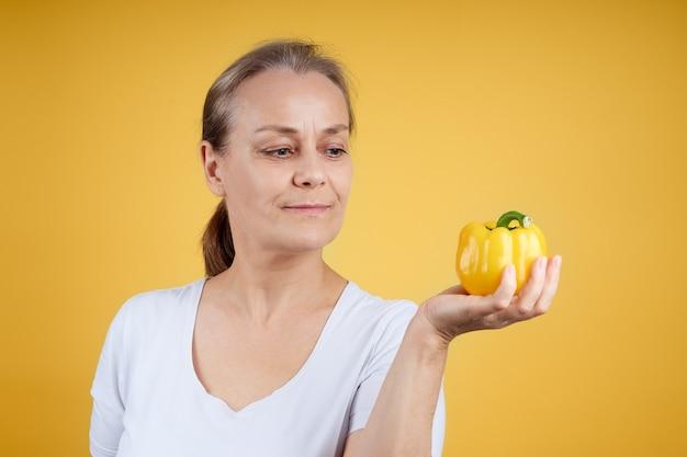 Een volwassen schattige huisvrouw in een wit overhemd heeft een gele paprika in haar hand