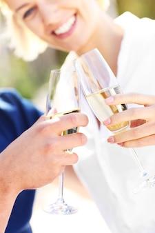 Een volwassen stel met glazen champagne op het strand