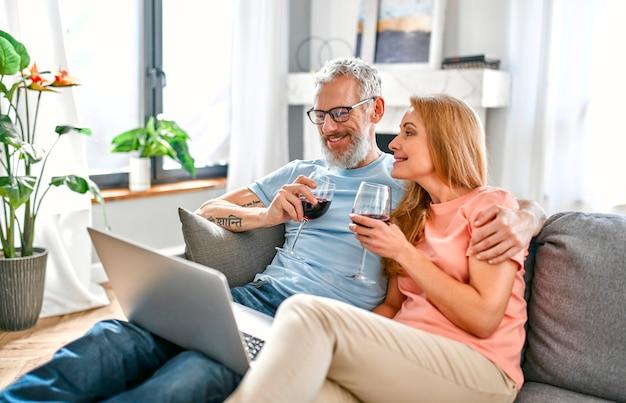 Een volwassen stel zit thuis op de bank met een laptop en glazen rode wijn.