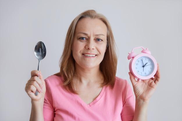 Een volwassen vrolijke vrouw houdt een wekker in haar hand, een lepel, kijkt in de camera, lunchtijd. foto op grijze achtergrond.