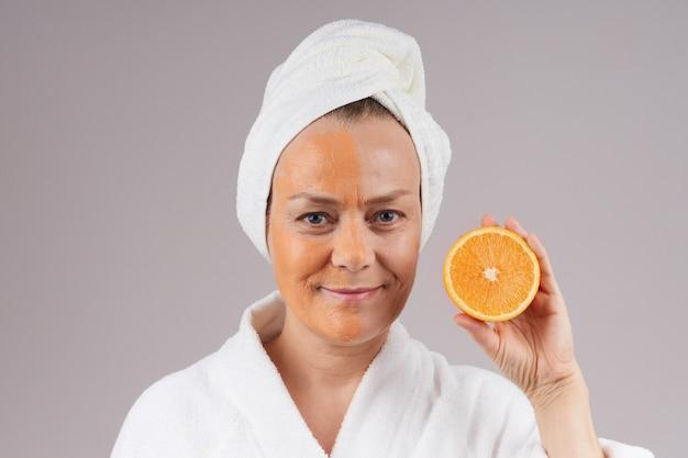 Een volwassen vrolijke vrouw in een gewaad, een witte handdoek over haar hoofd, een fruitmasker op haar gezicht, een sinaasappel in haar hand. gezichtsverzorging concept. over grijze muur.