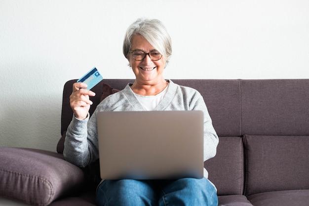 Een volwassen vrouw die alleen thuis plezier heeft met haar creditcard en haar laptop die online op de bank winkelt - senior shopaholic glimlachend en kijkend naar de computer