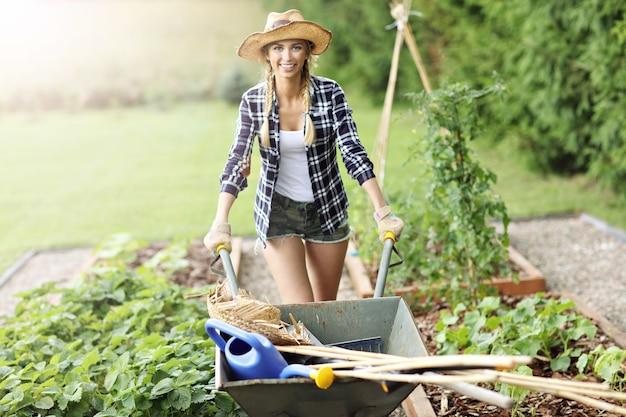 Een volwassen vrouw die groenten uit de tuin plukt