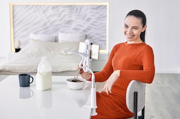Een volwassen vrouw gebruikt een telefoonhouder aan de eettafel