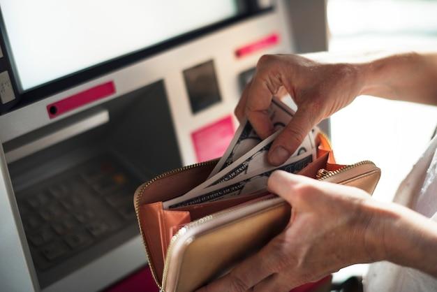 Een volwassen vrouw handen met contant geld bij atm