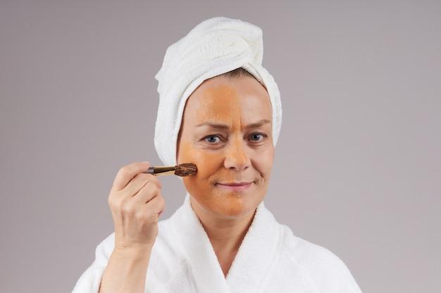 Een volwassen vrouw in een gewaad, een witte handdoek op haar hoofd, brengt een fruitoranje masker op haar gezicht aan. gezichtsverzorging concept. over grijze muur.