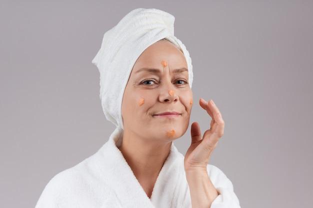 Een volwassen vrouw in een gewaad, een witte handdoek over haar hoofd, brengt oranje crème op haar gezicht aan. gezichtsverzorging concept. over grijze muur.
