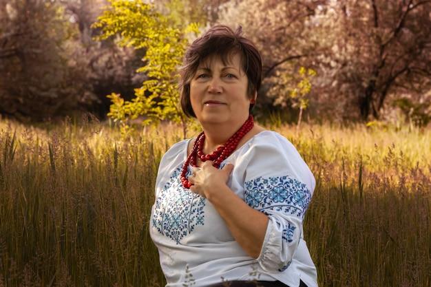 Een volwassen vrouw in een wit geborduurd overhemd zit in een veld tegen een achtergrond van bomen. een vrouw in een oude oekraïense nationale jurk.