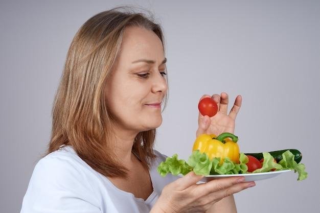 Een volwassen vrouw in een wit overhemd houdt een bord groenten vast, staat in profiel