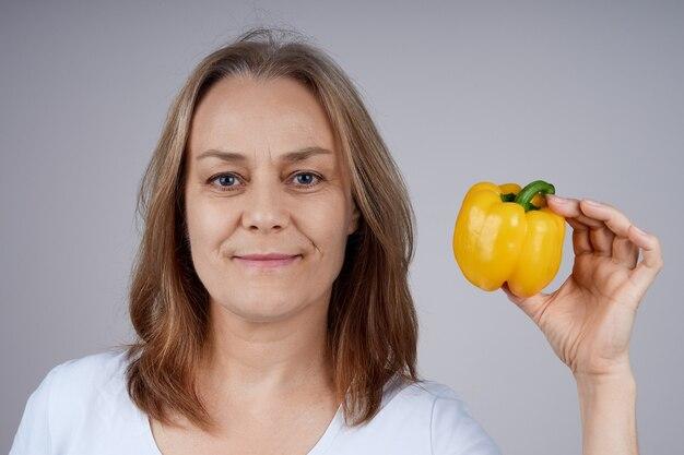 Een volwassen vrouw in een wit overhemd houdt een gele paprika in haar hand, kijkt in de camera