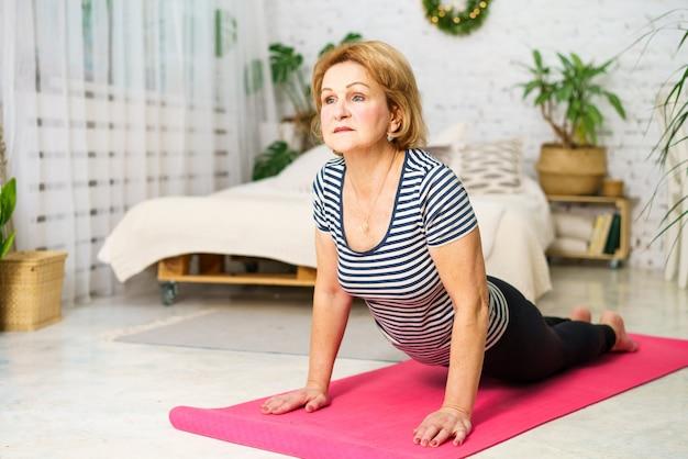 Een volwassen vrouw met een blanke uitstraling sport thuis in sportkleding op de mat