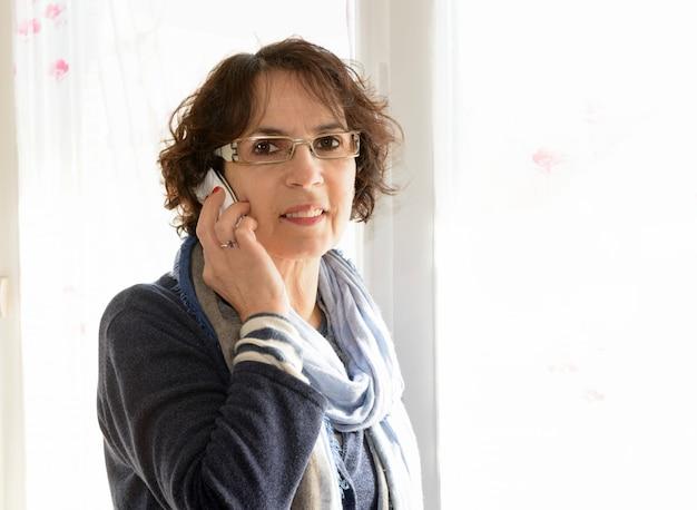 Een volwassen vrouw met een mobiele telefoon