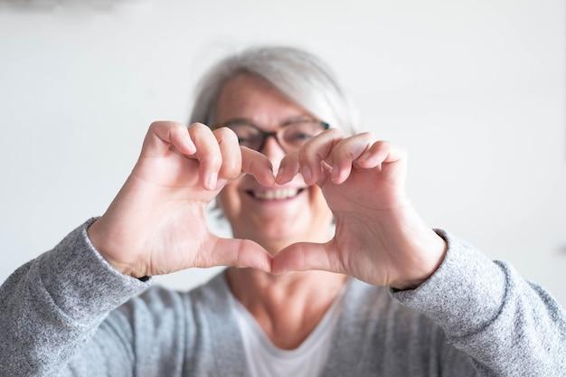 Een volwassen vrouw of senior die thuis een hart doet met haar handen en vingers - gelukkige gepensioneerde