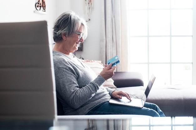Een volwassen vrouw op de bank die haar laptop en haar creditcard gebruikt om iets te kopen - online winkelconcept en shopaholic - senior thuis die geschenken en cadeautjes doet met de verkoop