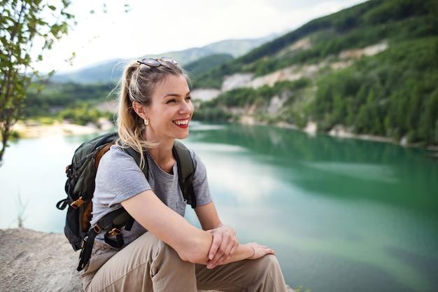 Een volwassen vrouw toerist op wandeltocht op zomervakantie, rustend aan het meer.