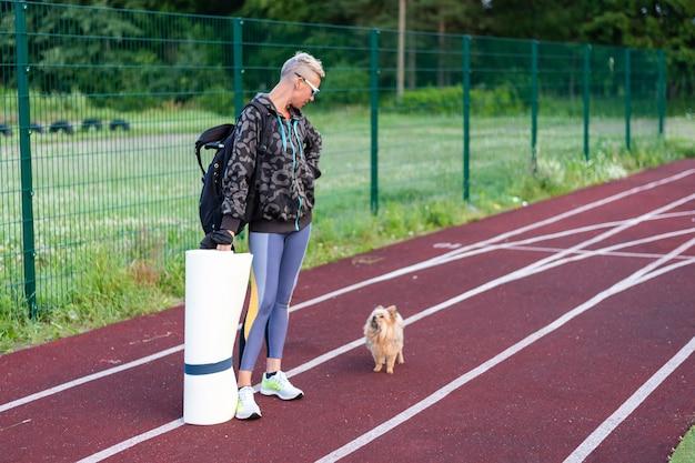 Een volwassen vrouw traint in het stadion, samen met een hondje. voor elk doel.