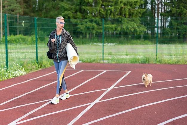 Een volwassen vrouw traint in het stadion, samen met een hondje. voor welk doel dan ook.
