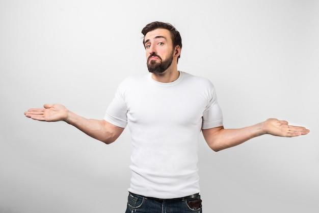 Een volwassene die in de buurt van de witte muur staat met een droevig gezicht en laat zien dat hij op dit moment niets bij zich heeft of niets weet. hij kijkt recht vooruit. geïsoleerd op witte muur.