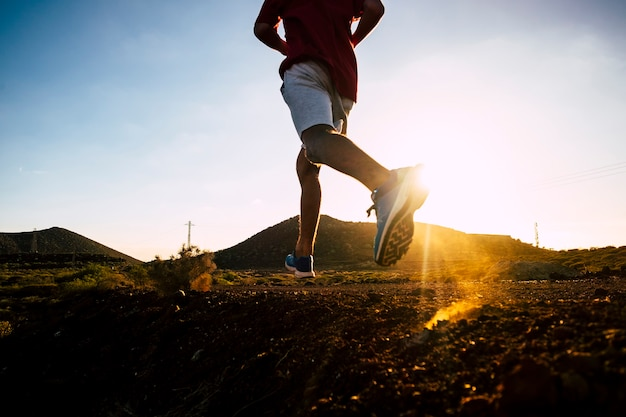 Een volwassene loopt met joggingkleding alleen in de bergen bij de zonsondergang - tienerfitness die geïsoleerde oefeningen doet