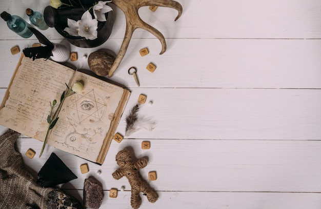 Een voodoo-pop gemaakt van touw ligt met een oud boek grimoire, omringd door magische rituele objecten, plat gelegd