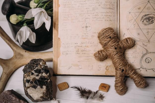 Een voodoo-pop gemaakt van touw ligt met een oud boek grimoire