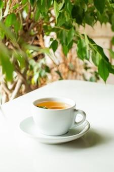 Een voor dichte omhooggaande hete thee binnen witte kop op de witte vloer