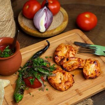 Een voor dichte omhooggaande mening gebraden kip samen met verse groenten op het bruine houten bureau