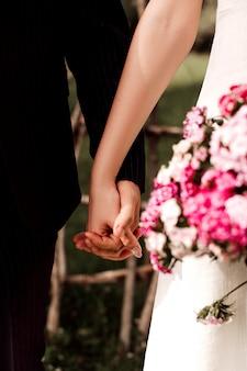 Een voor dichte omhooggaande meningspaar die van man en vrouw elkaars handen houden tijdens huwelijk