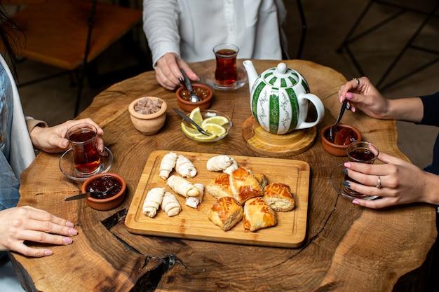 Een voor dichte omhooggaande vrienden die van de theeceremonie hete thee drinken en jam eten