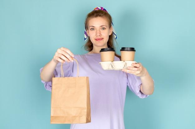Een vooraanzicht aantrekkelijk vrouw in blauwe overhemdjurk met papieren pakket en koffiekopjes op blauw