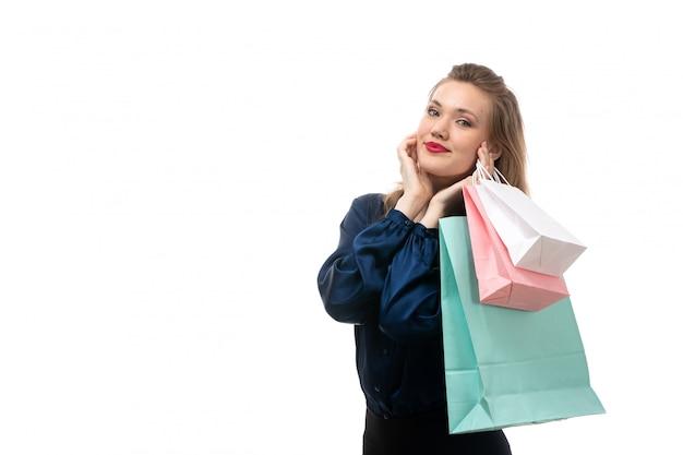 Een vooraanzicht aantrekkelijke jonge dame in blauwe blouse zwarte broek poseren met shopping pakketten glimlachend gelukkig op de witte achtergrond mode elegante kleding