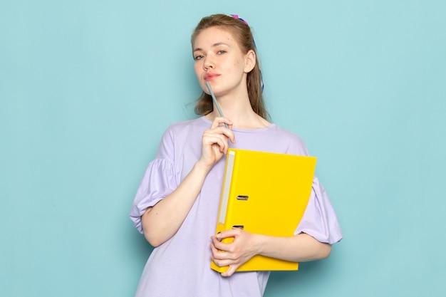 Een vooraanzicht aantrekkelijke vrouw in blauwe hemd-jurk met gele bestanden op blauw
