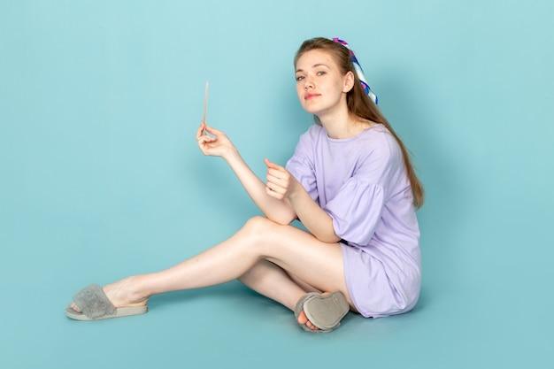Een vooraanzicht aantrekkelijke vrouw in blauwe hemd-jurk werkt met haar nagels op blauw