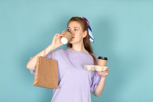 Een vooraanzicht aantrekkelijke vrouw in blauwe overhemdjurk met papieren pakket en koffiekopjes drinken op blauw