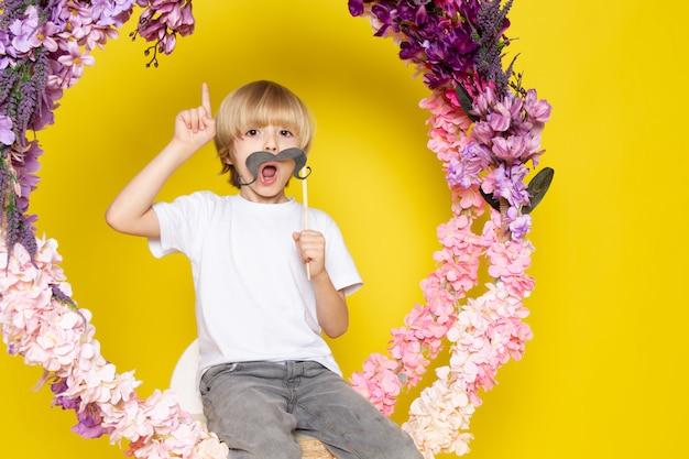 Een vooraanzicht blonde jongen grappig in wit t-shirt op de gele ruimte