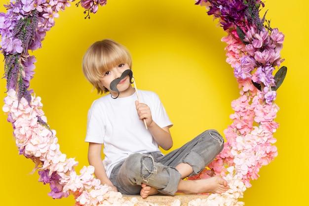 Een vooraanzicht blonde jongen in wit t-shirt en snor op de gele ruimte