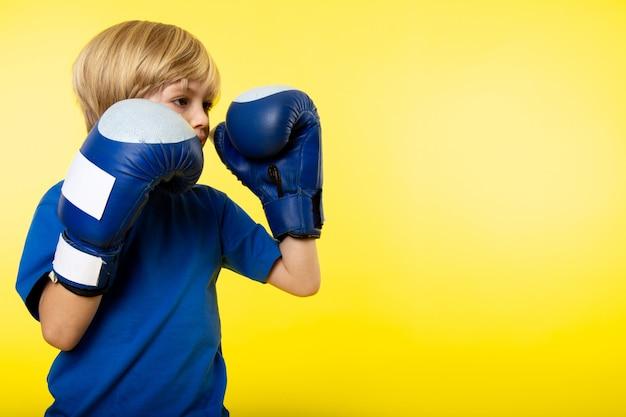 Een vooraanzicht blonde jongen poseren boksen in blauwe bokshandschoenen op de gele muur